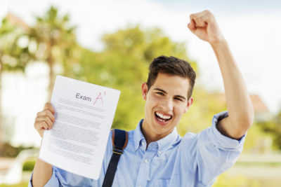 Student Clenching Fist While Holding Exam Paper With A+ Grade